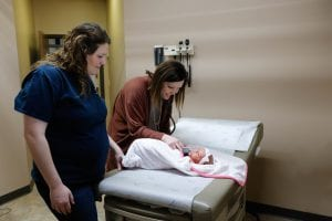 Jessica Duncan, FNP examining baby with mother nearby
